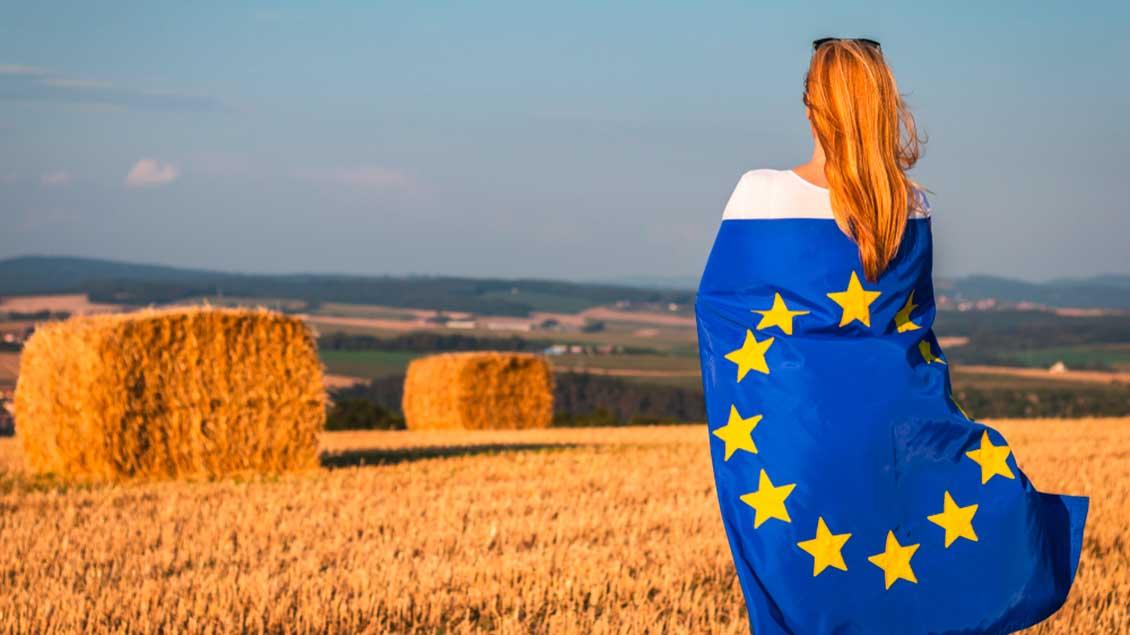 Frau mit Europa-Fahne auf einem abgteernteten Getreidefeld