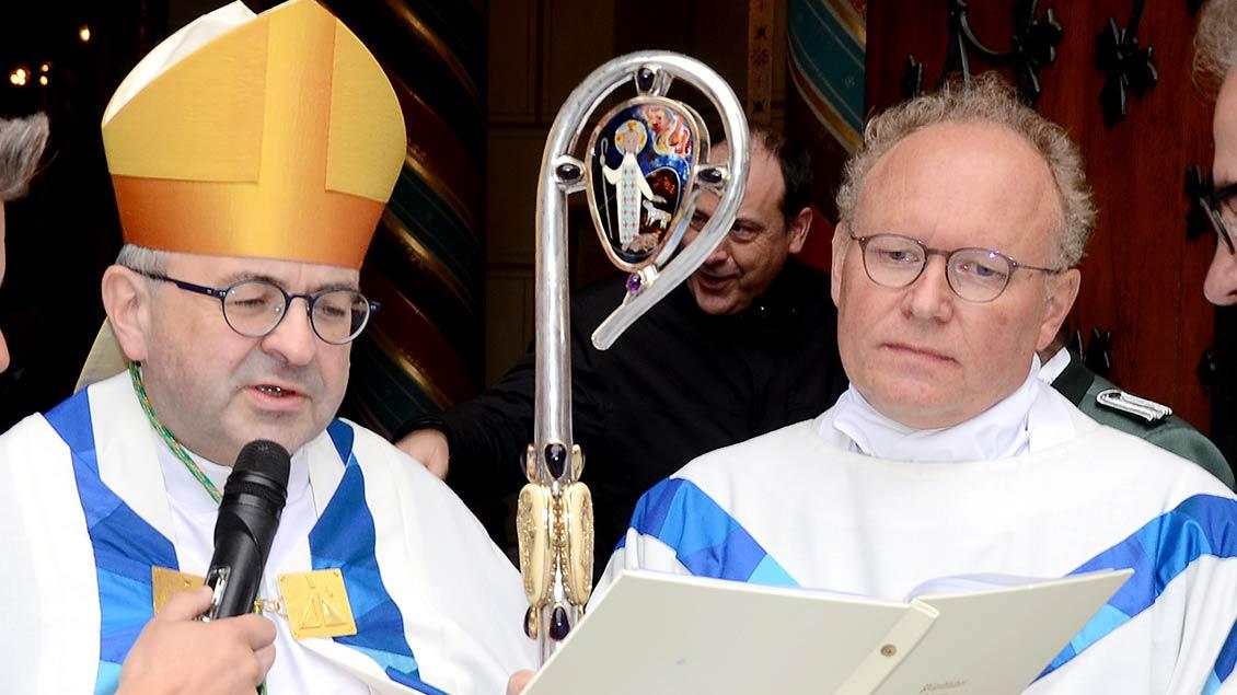 Bischof Harrie Smeets und Wallfahrtsrektor Gregor Kauling stehen vor der Pilgerpforte in Kevelaer.