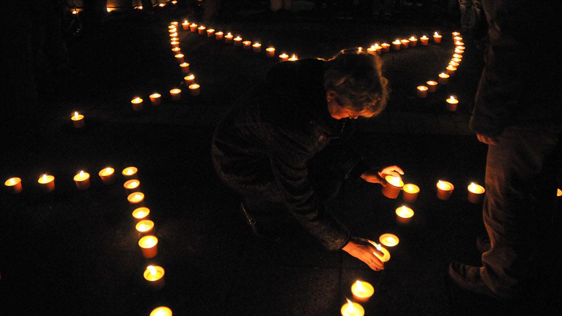 Kerzen im Dunkeln bilden einen Stern.
