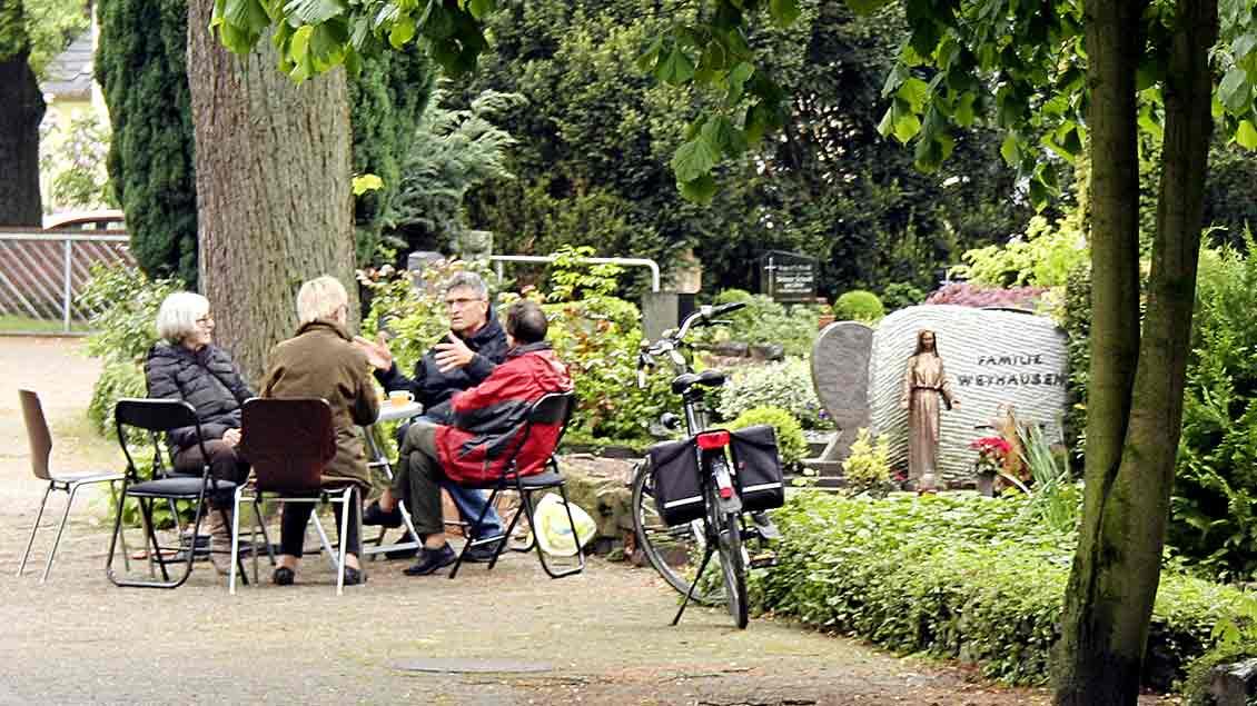 """Eine Gruppe von Menschen sitzt auf Klappstühlen auf dem Katholischen Friedhof in Oldenburg zusammen. Das Projekt dort heißt """"Café der Erinnerung""""."""