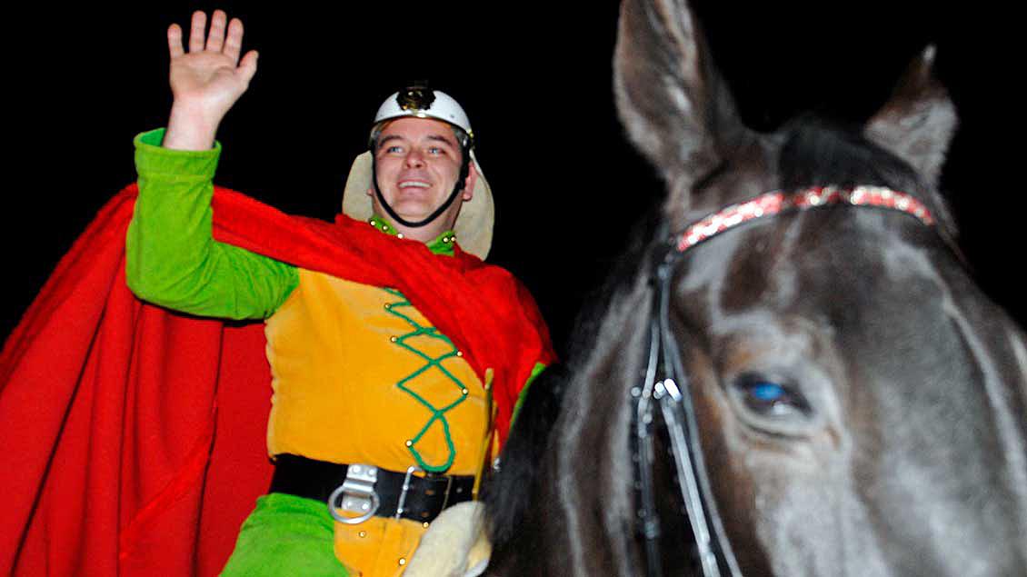 Ein Mann sitzt, als St. Martin gekleidet, auf einem Pferd.