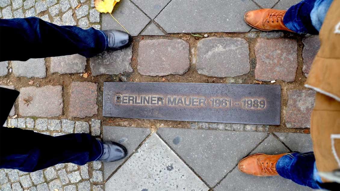 zwei paar Füße von oben fotografiert, dazwischen verläuft eine Gedenklinie zur Berliner Mauer.