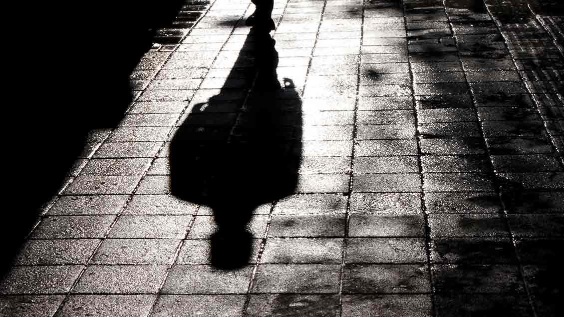 Der Schatten eines Mannes fällt auf eine dunkle Straße.