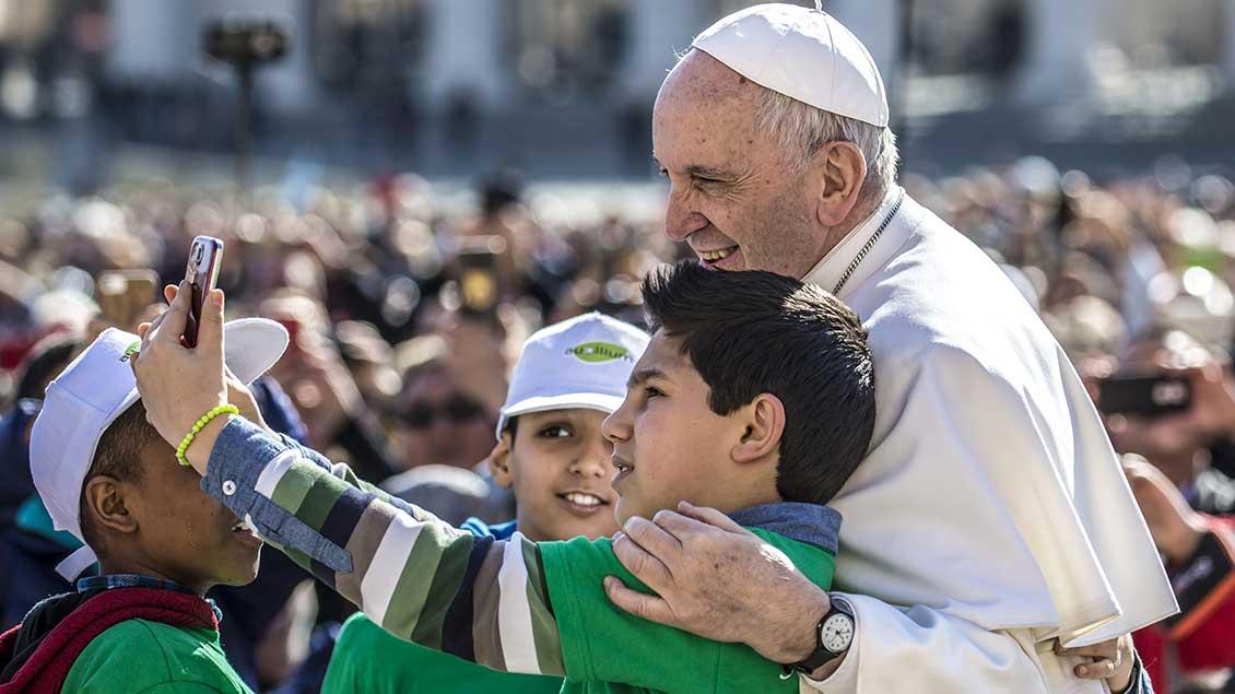 Drei Jungen machen mit einem Smartphone ein Foto mit Papst Franziskus auf dem Petersplatz.
