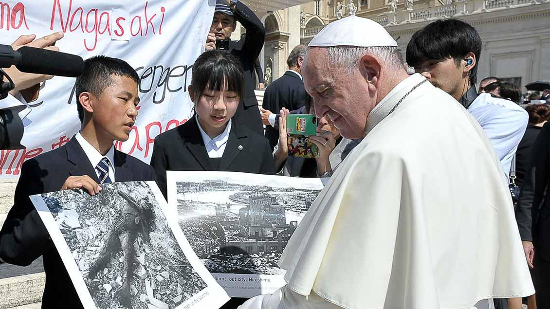 Papst Franziskus mit jungen Menschen aus Hiroshima und Nagasaki, die ihm Fotos nach den Atombombenabwürfen 1945 zeigen