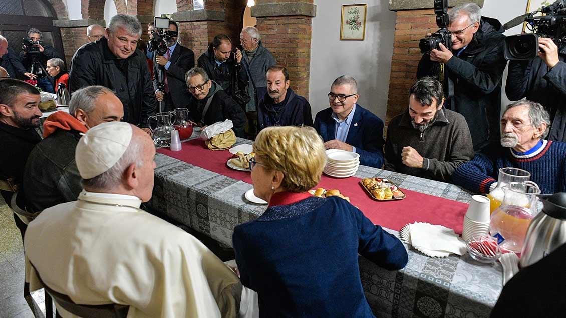 Der Papst sitzt am Tisch in der Obdachlosenunterkunft im Palazzo Migliori.
