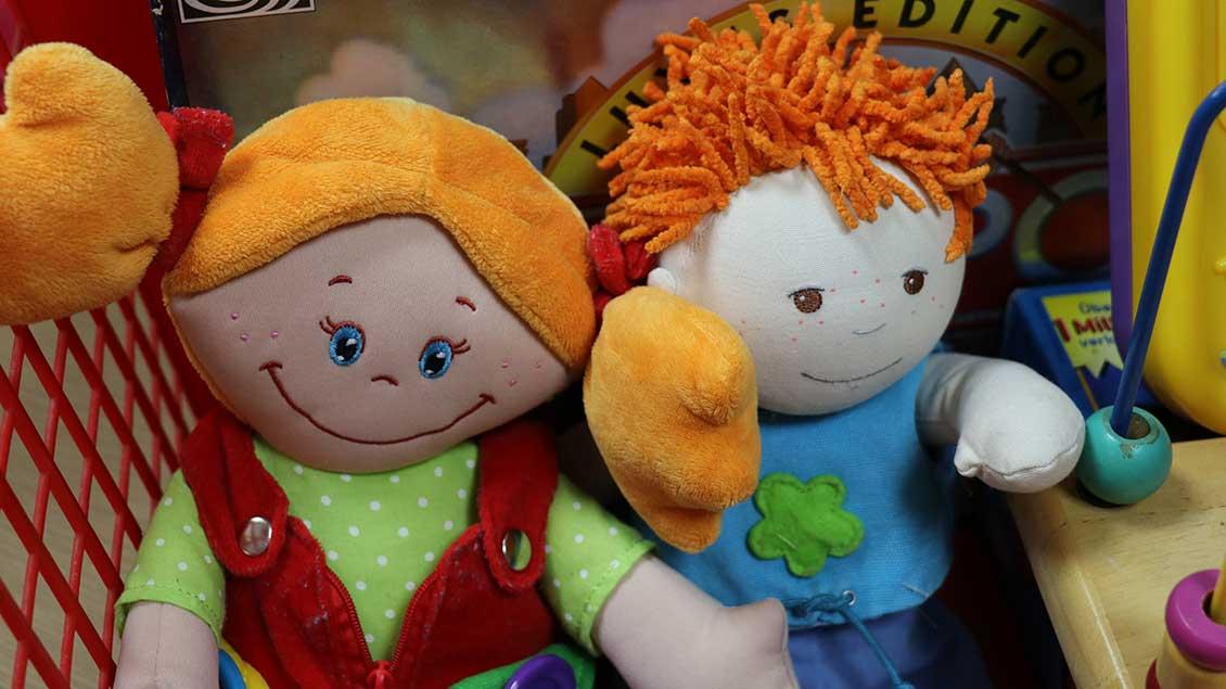 Zwei Puppen mit bunten Kleidern stehen in einem Regal zum Verkauf.