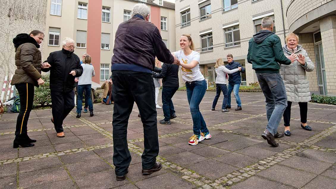 Frauen und Männer tanzen vor der Raphaelsklinik Münster