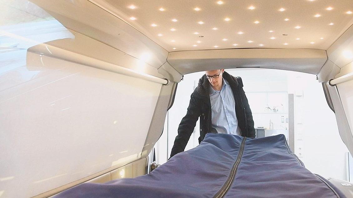 Der Bestatter Steffen Hackmann zeiht eine Trage aus seinem Leichenwagen.