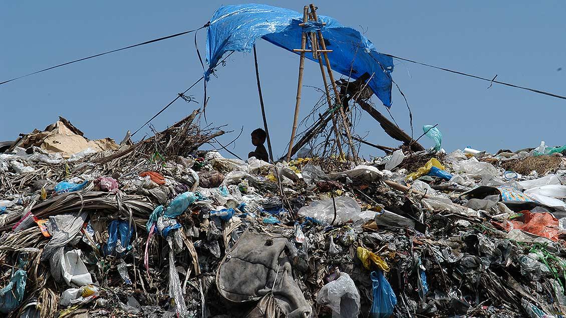 Auf einer Müllhalde auf dem Philippinen sitzt ein Kind unter einem primitiven Sonnensegel.