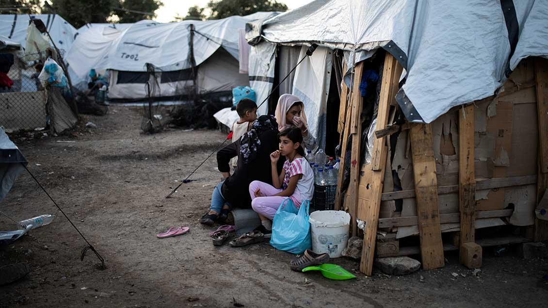Provisorisches Flüchtlingslager auf Lesbos. Frauen und Kinder sitzen vor den Hütten.