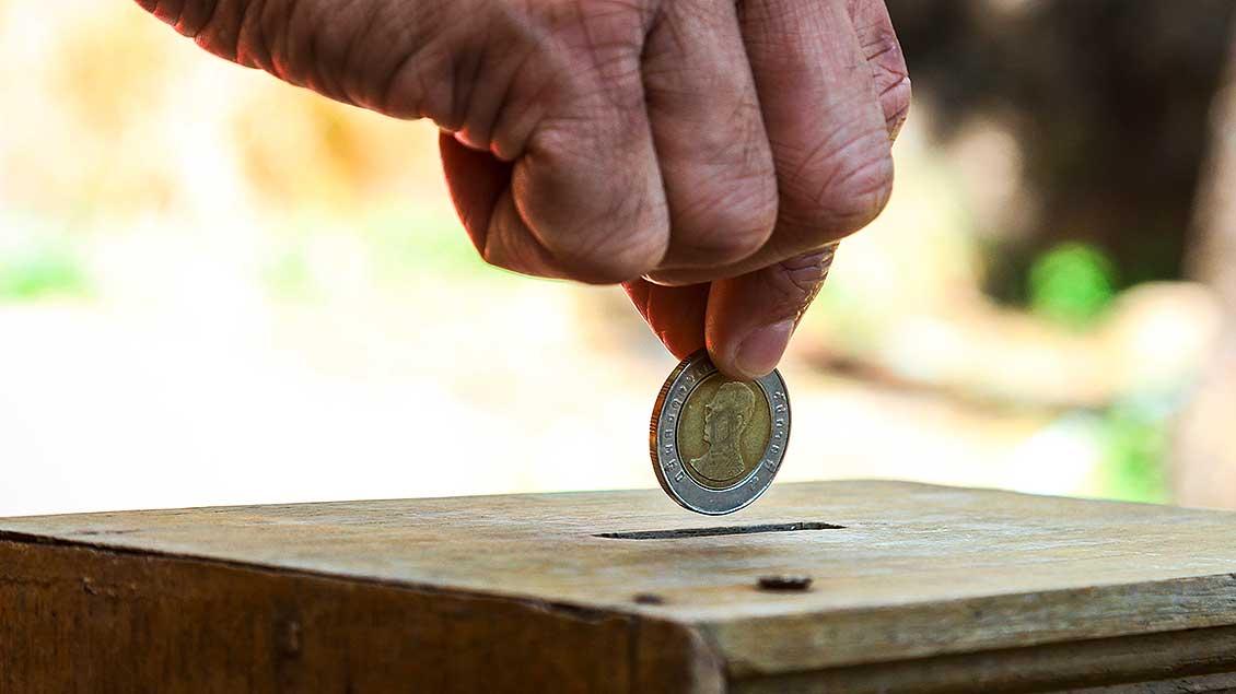 Eine Hand steckt eine Münze in eine Spendenbox