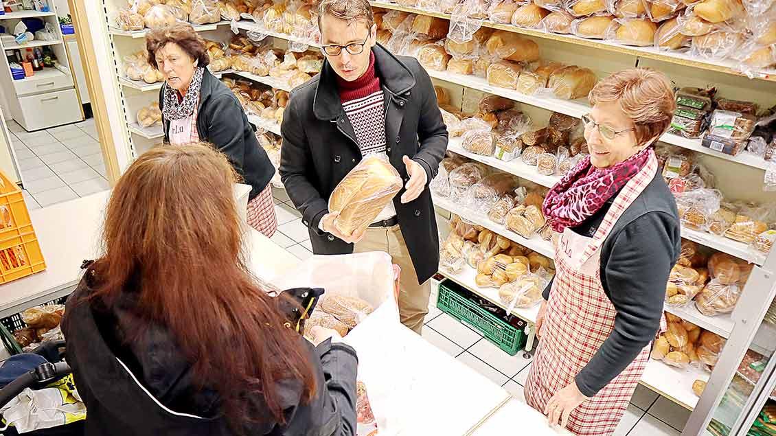 Kaplan Cosmin Croitoru steht zwischen zwei Helferinnen an der Brotausgabe und reicht einer Kundin einen Laib Brot.