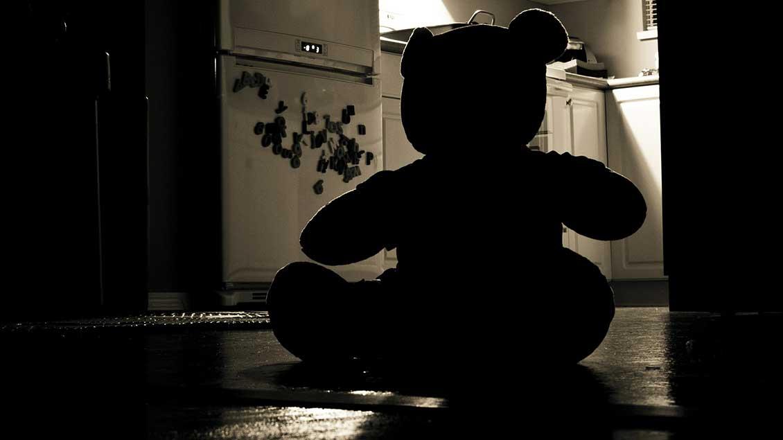 Silhuette eines Teddybärs auf dem Boden.