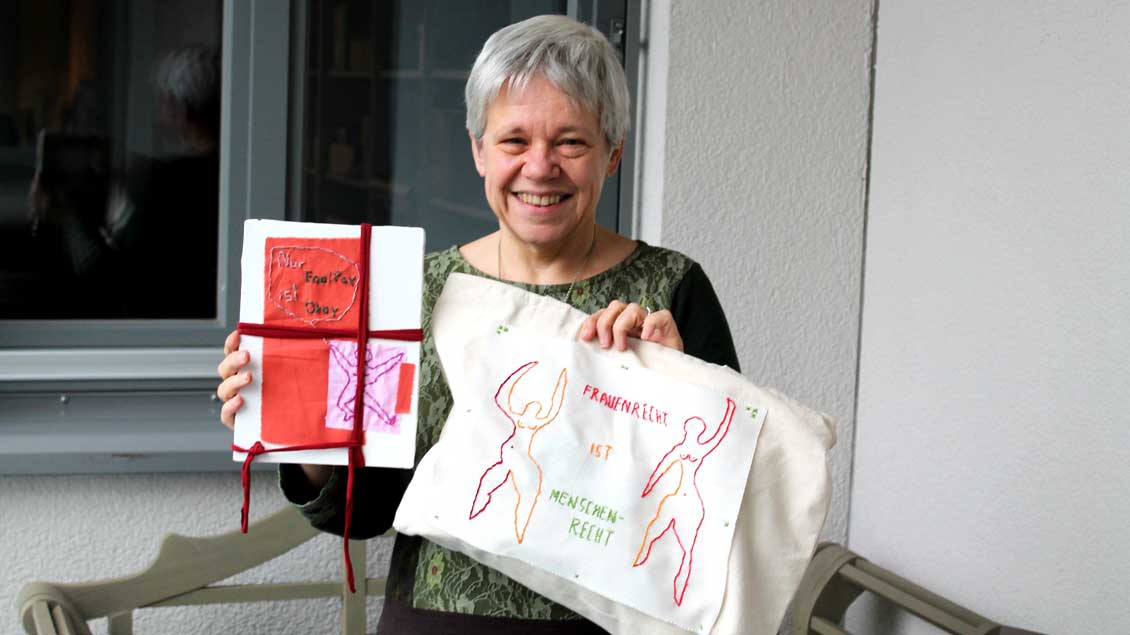 Eine Frau zeigt eine bestickte Leinwand und eine Tasche.