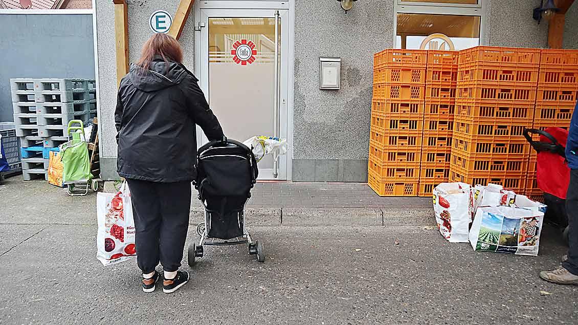 Eine Frau steht vor der Eingangstür der Caritas-TAfel in Friesoythe. Rechts und links sieht man Transportkisten.