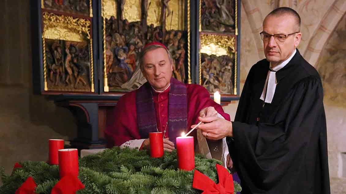 Weihbischof Wilfried Theising (links) und der evangelische Landesbischof von Oldenburg, Thomas Adomeit, entzünden bei einem ökumenischen Gottesdienst in Stuhr die erste Kerze am Adventskranz.