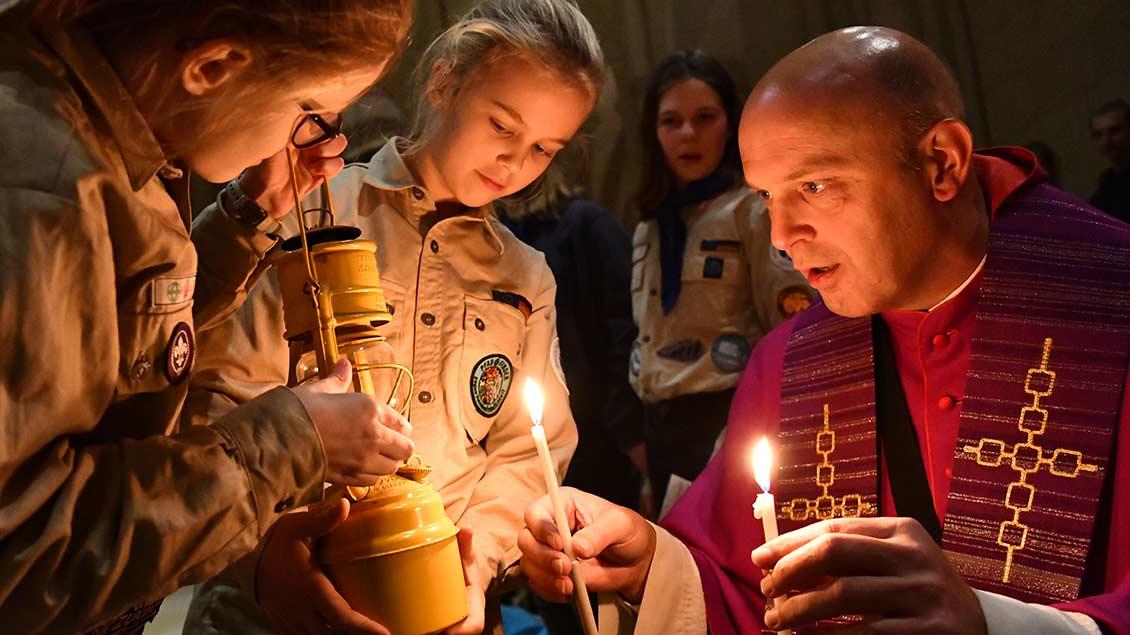 Dompropst Kurt Schulte entzündet Kerzen junger Pfadfinder.