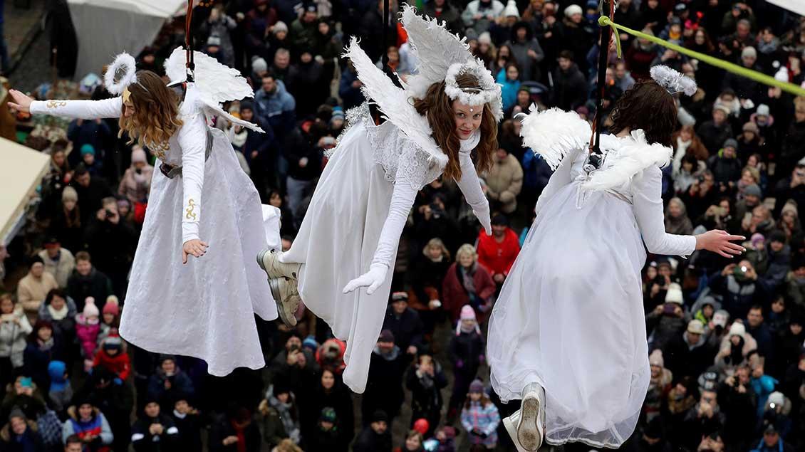 Als Engel verkleidete junge Frauen schweben über den Besuchern des Weihnachtsmarkts der tschechischen Stadt Ustek.