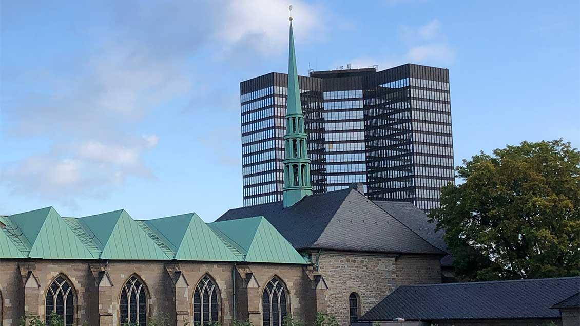 Kirche vor Hochhaus.