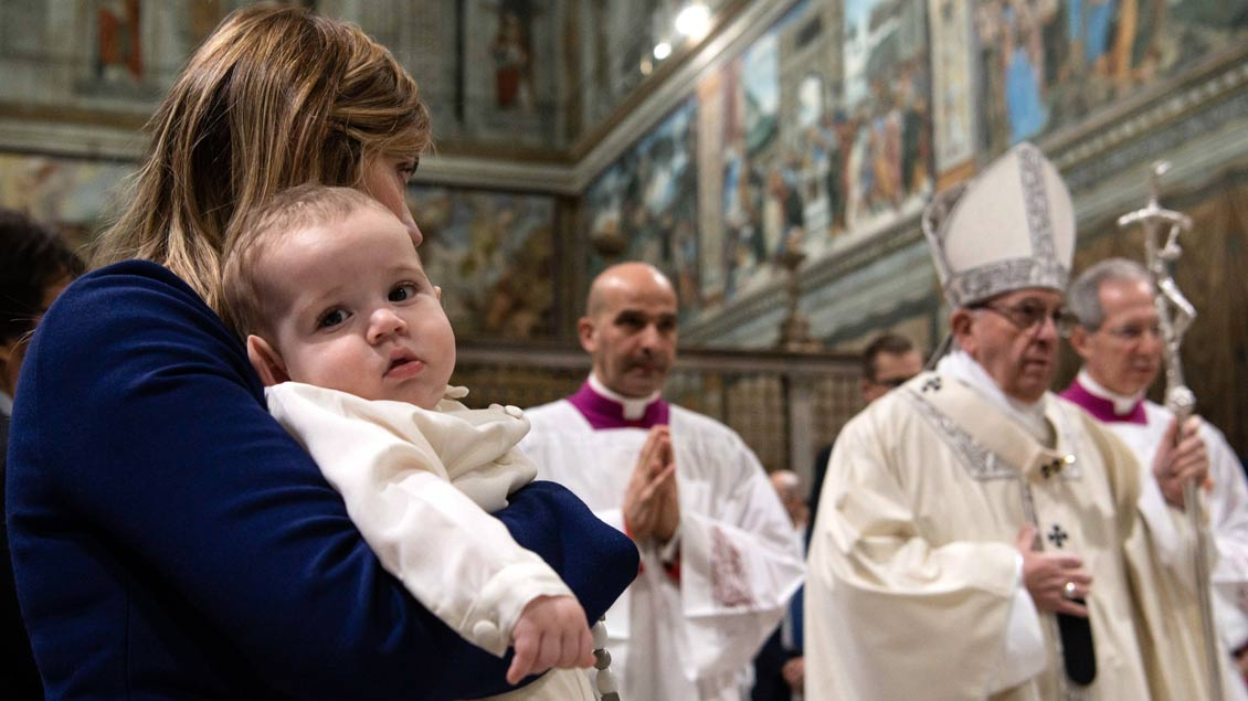 Kind schaut in der Sixtinischen Kapelle in die Kamera.