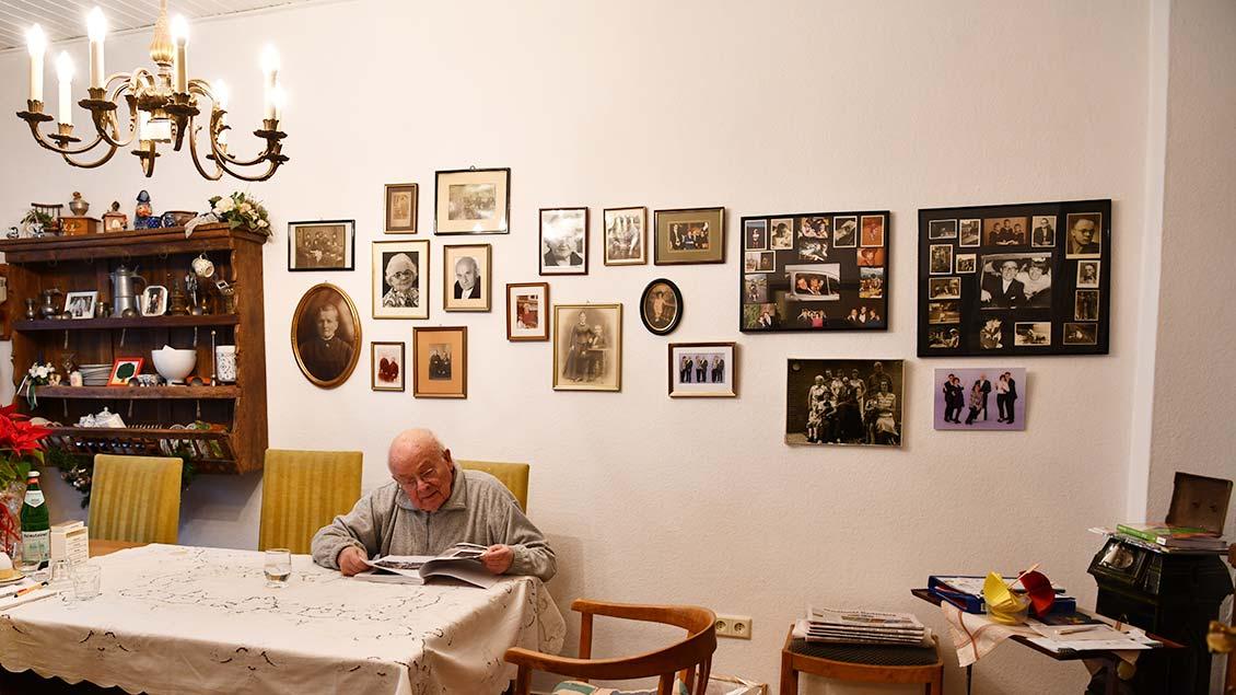 Paul Remmeke blättert am Esstisch in seiner Wohnung in Münster durch sein Erinnerungs-Buch.