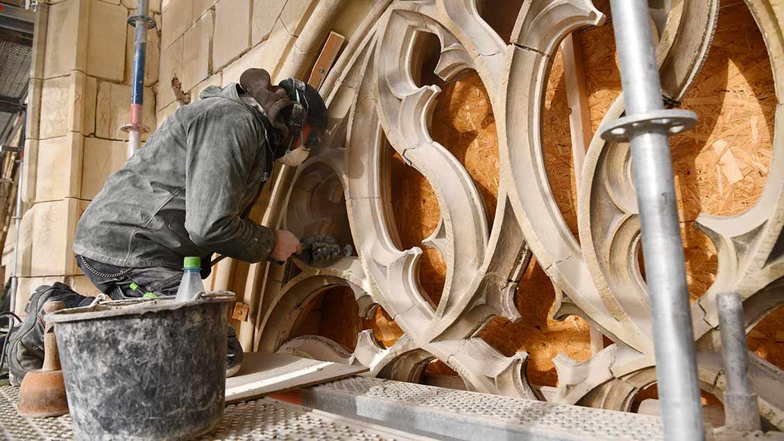 Ein Handwerker schleift ein Relief des Domportals in Münster