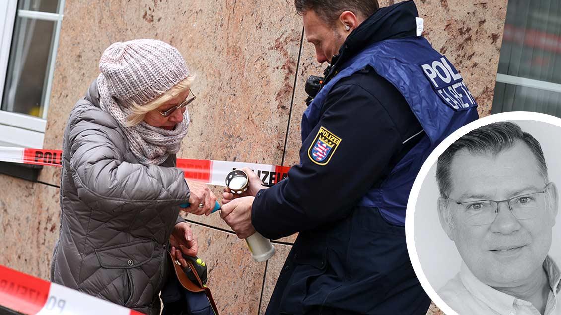 Ein Polizist hilft einer Frau in Hanau, eine Kerze anzuzünden.