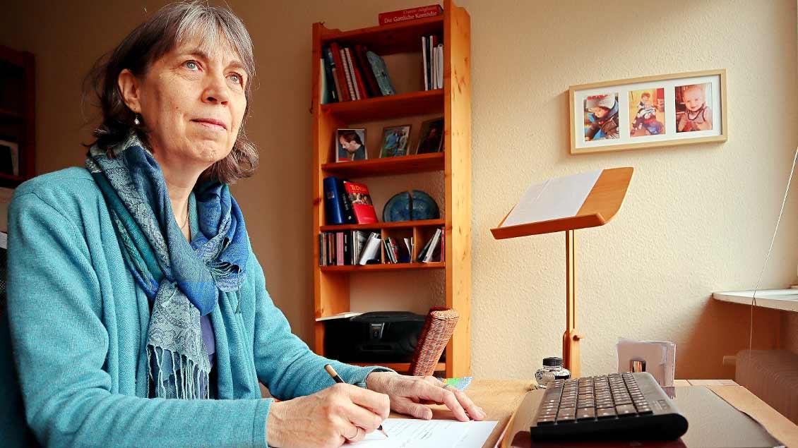 Lisa Oesterheld sitzt vor einem Schreibblock zu Hause an ihrem Schreibtisch.