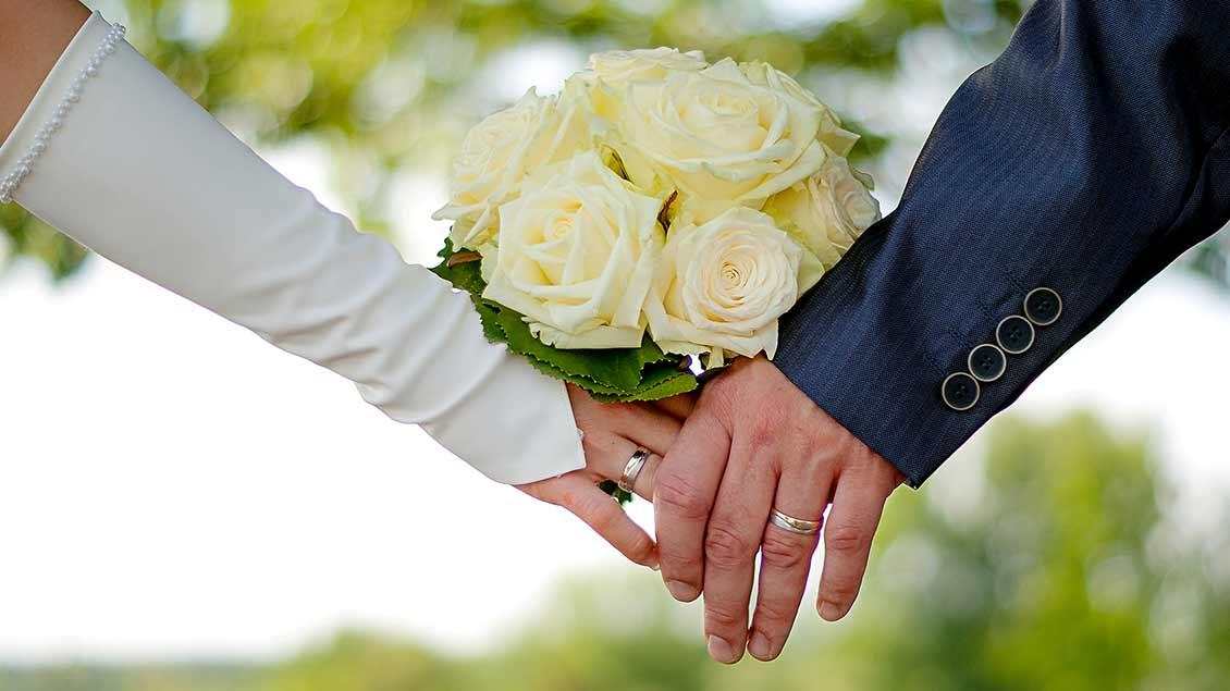 Ein Hochzeitspaar hält sich an den Händen. Das Zeichen, dass beide die Liebe gefunden haben.