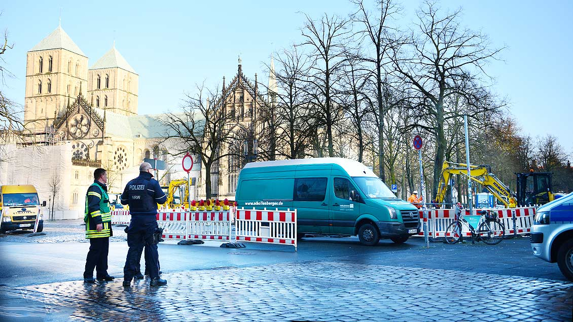 Polizisten und Feuerwehrleute stehen vor eine Baugrube auf dem Domplatz in Münster. Foto: Michael Bönte