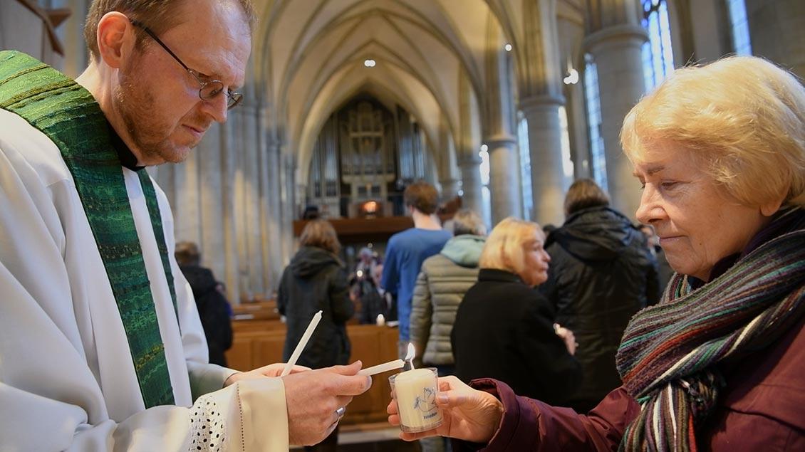 Stadtdechant Hagemann entzündet beim Friedensgebet in Münster die Kerze einer Gottesdienstteilnehmerin.