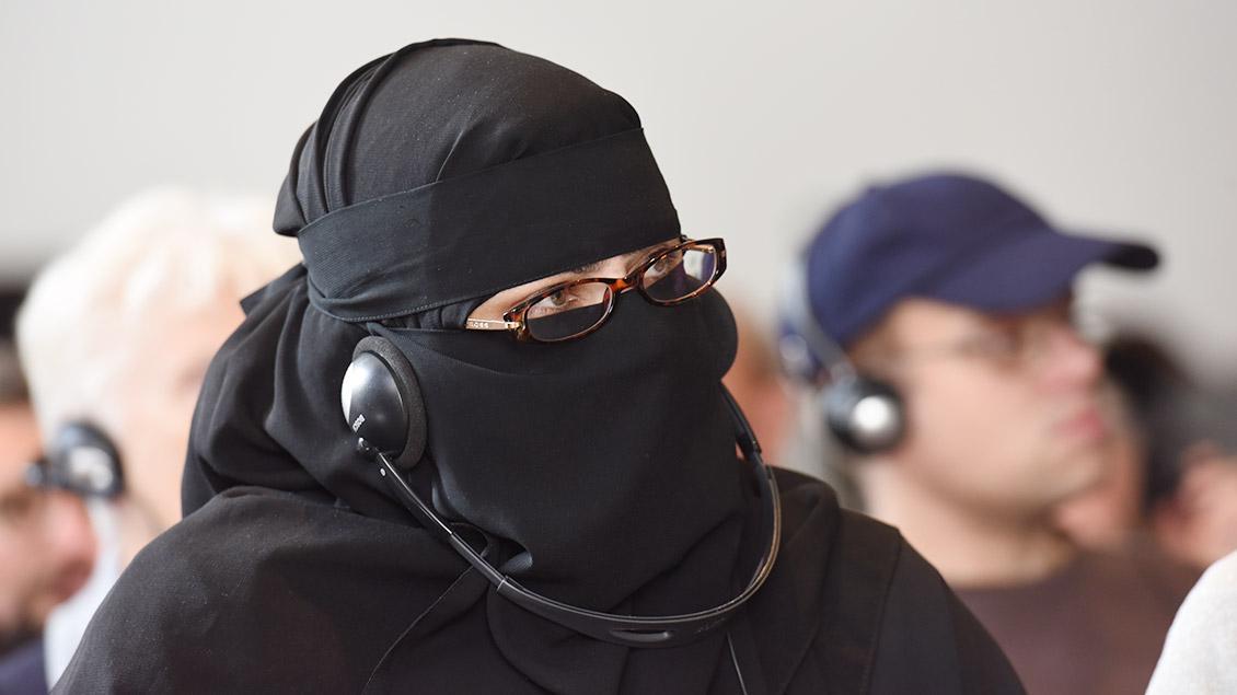 Eine Frau mit Vollverschleiderung sitzt mit einem Kopfhörer in einem Hörsaal.