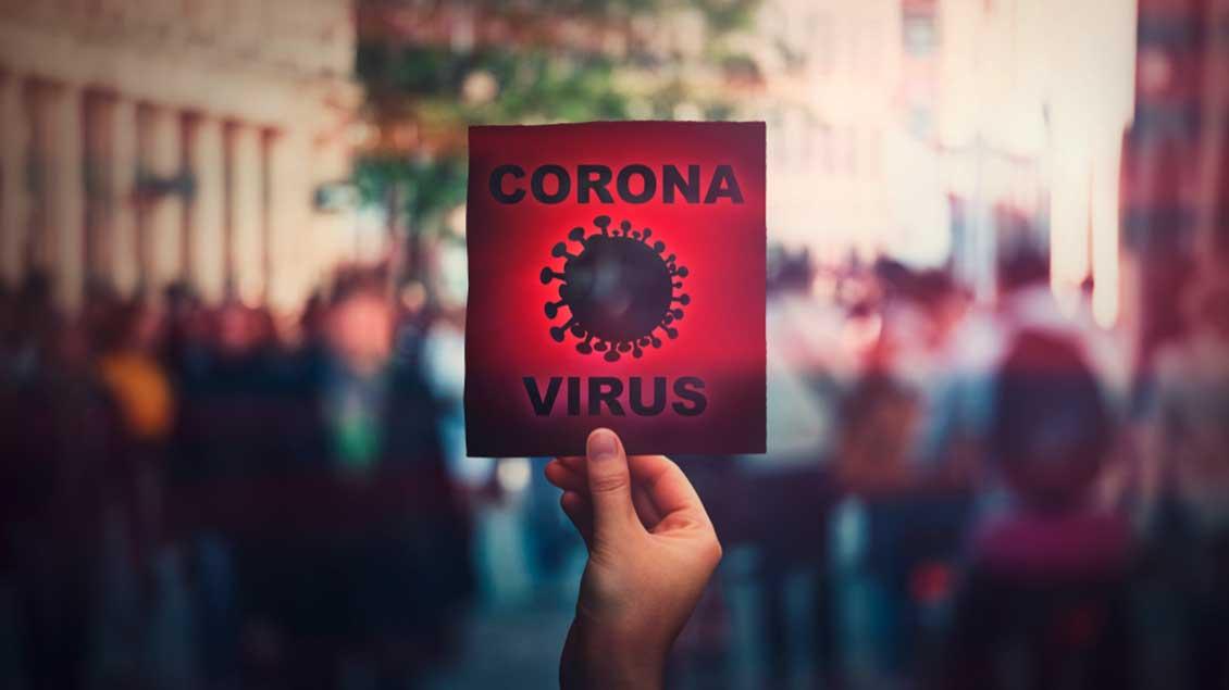 Schild: Corona-Virus vor Menschenmenge