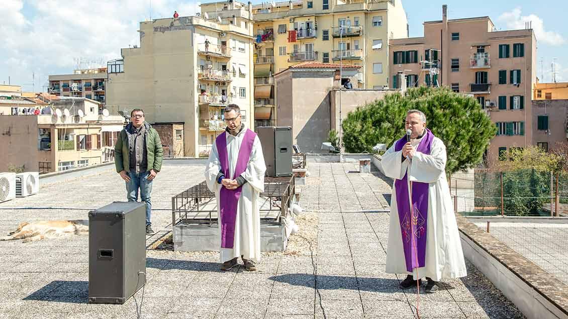 Zwei Priester feiern in Rom Gottesdienst auf dem Dach