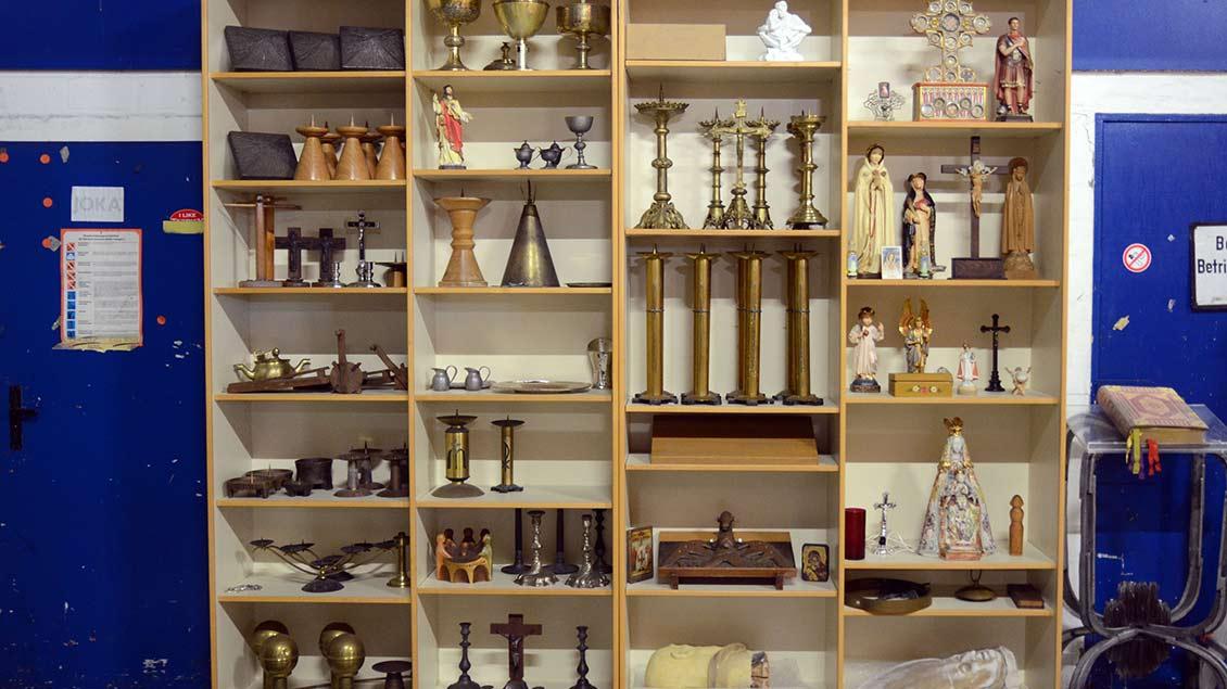 Kelche, Heiligenfiguren und Kerzenleuchter lagern wie in einem Setzkasten