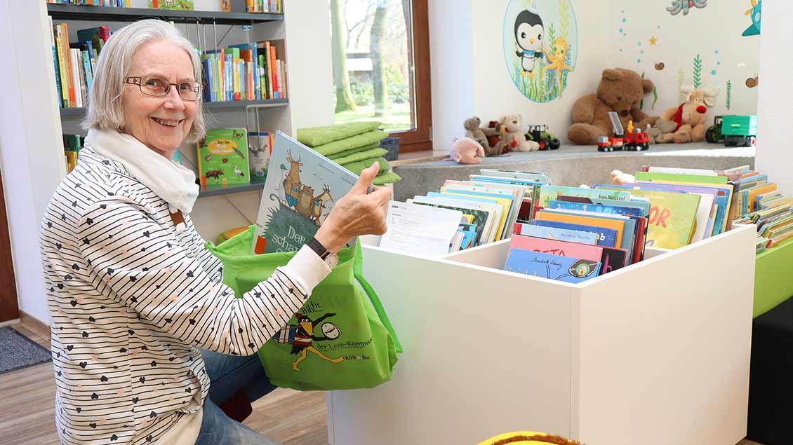 Bücherei-Leiterin Ulla Moormann packt ein Buchpaket.