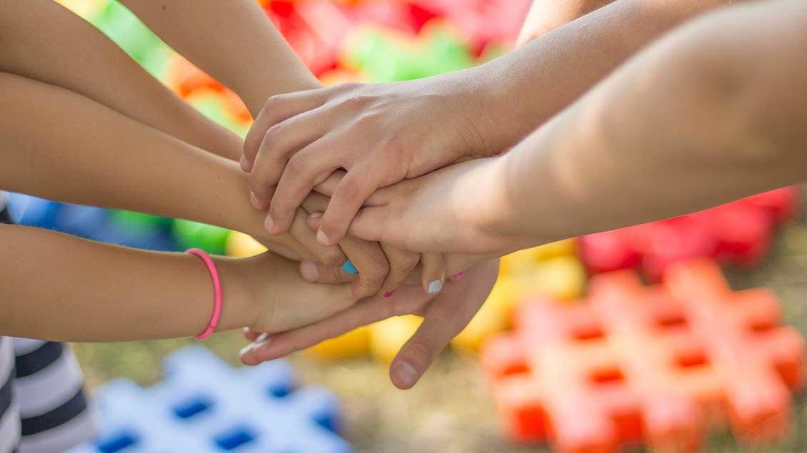 Mehrere Hände übereinander: Zusammenhalt