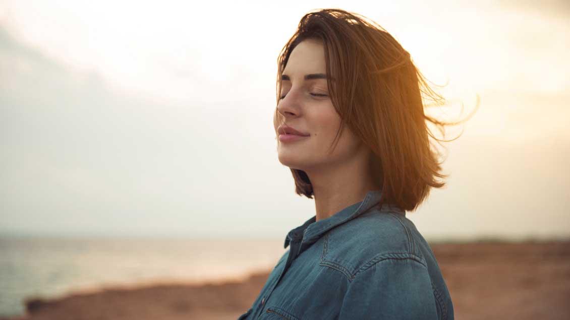 Eine Frau lächelt mit geschlossenen Augen in sich hinein