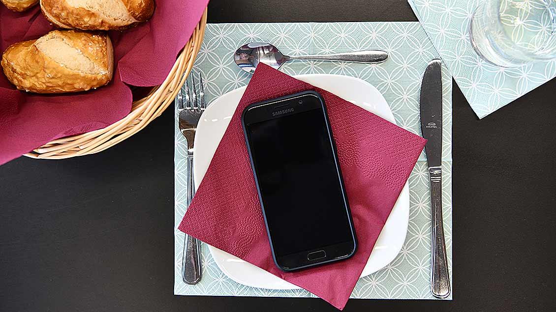 Ein Smartphone auf einem Teller.