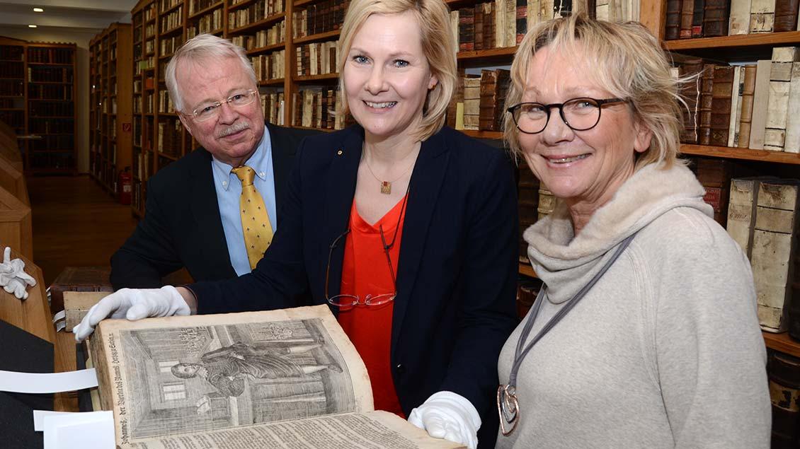 Hans-Wilhem Barking und Angelika Krull übergeben Elisabeth Maas die Lutherbibel.