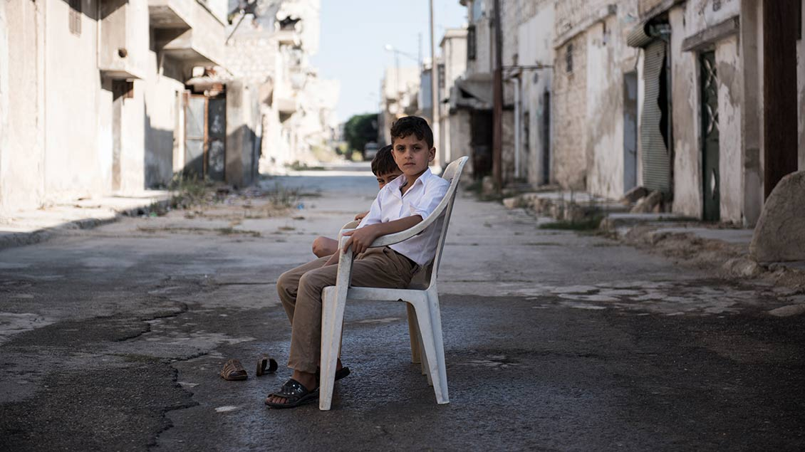 Ein Junge auf einer Straße mit zerstörten Häusern in Syrien