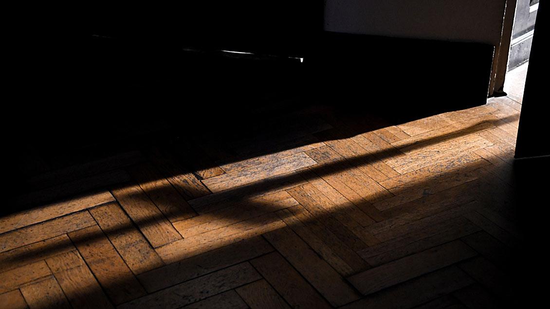 Symbolfoto: Geöffnete Kirchentür mit Schatten eines Kreuzes