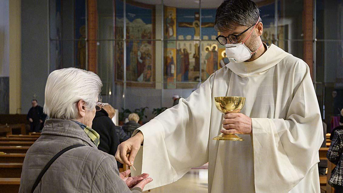 Ein Priester mit Mundschutz spendet in Rom einer Frau die Kommunion