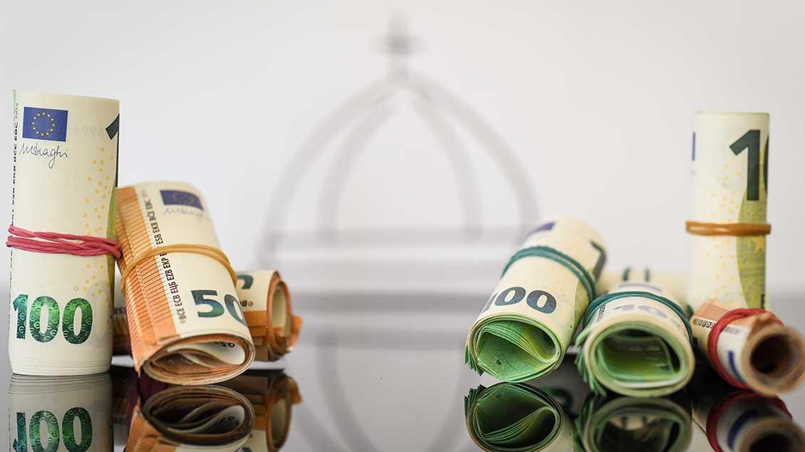 Geld vor einem Kirchensymbol