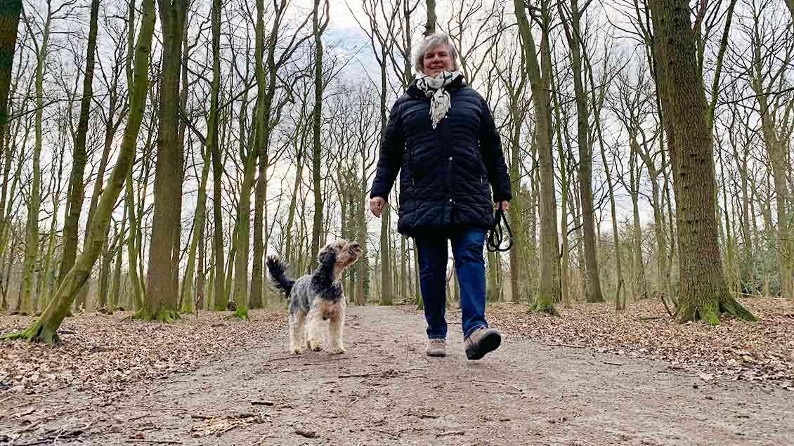 Monika Vernauer mit ihrem Hund Eddi im Wald.
