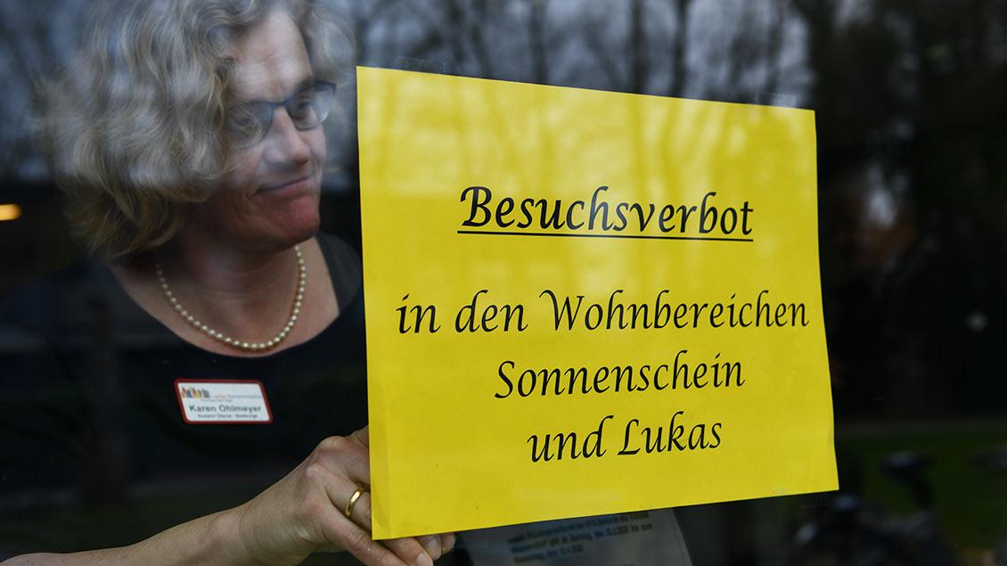 Eine Mitarbeiterin hängt ein Schild in eine Fenster, auf dem das Besuchsverbot bekannnt gegeben wird.