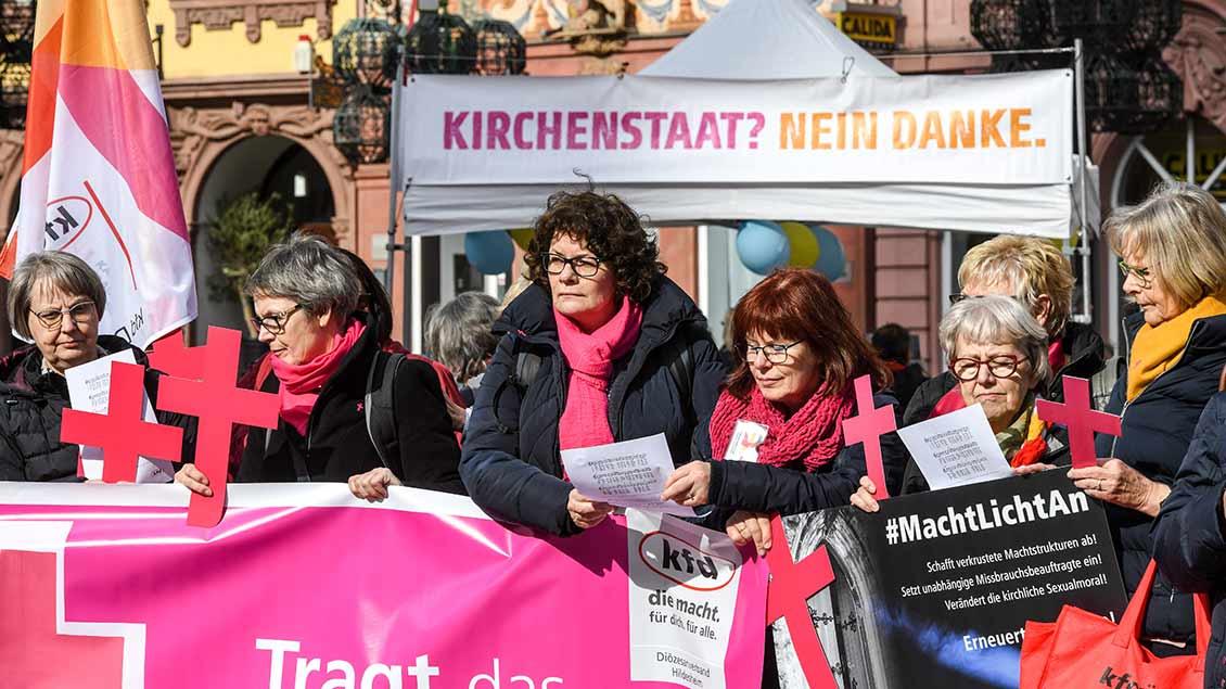 Frauen halten bei der DBK-Vollversammlung in Mainz Protest-Plakate in die Höhe.