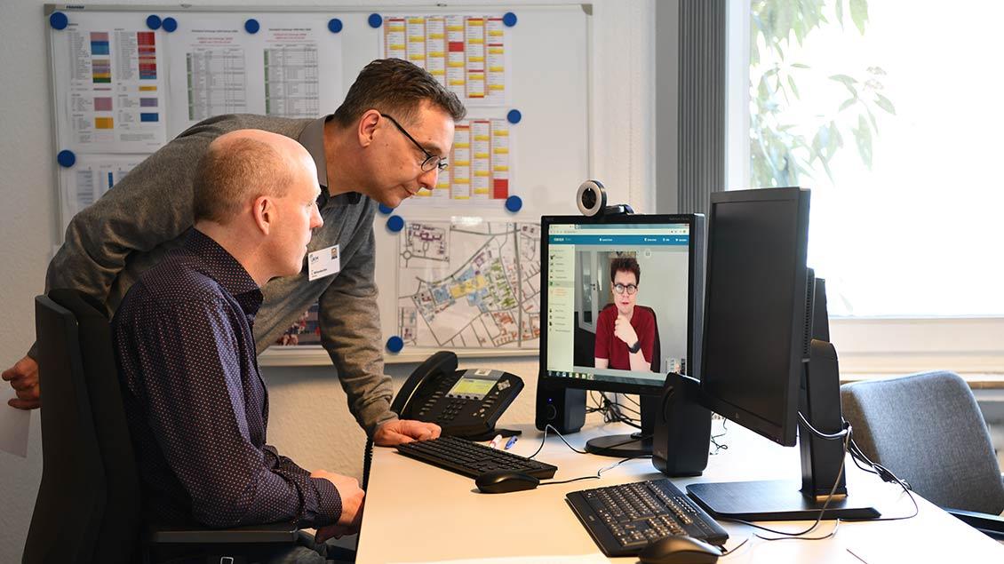 Klinikpfarrer Wittenbecher und Diakon Wiltink sitzen am Schreibtisch und sprechen über den Computer-Bildschirm mit Dr. Lenz.