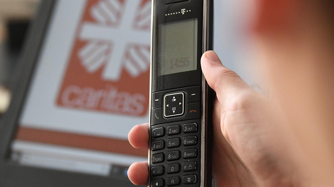 Ein Telefon mit dem Logo der Caritas im Hintergrund